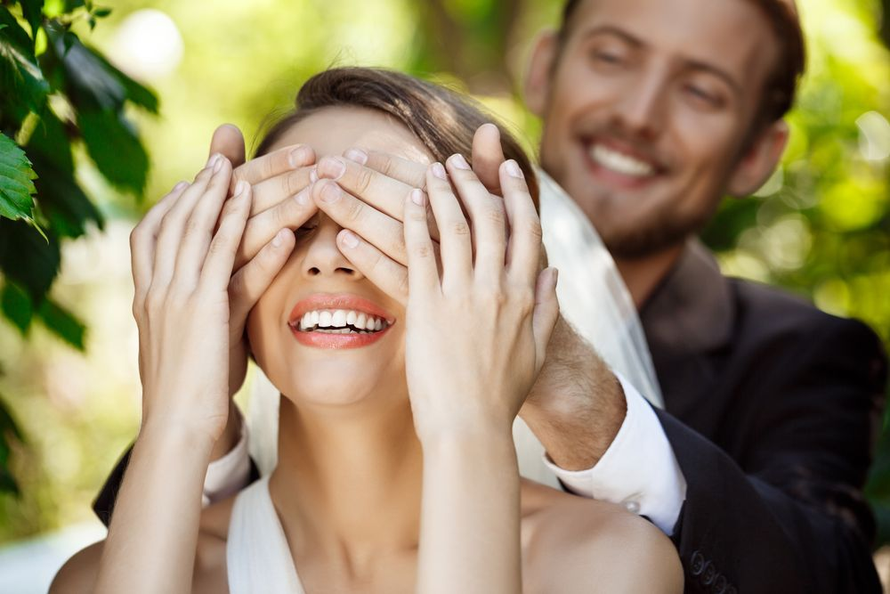 couple-newlyweds-smiling-groom-covering-bride-s-eyes-with-hands 2